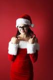 Stående av en härlig kvinna som vrider hennes hår runt om henne fingrar som bär Santa Claus kläder Arkivbild