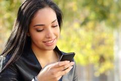 Stående av en härlig kvinnamaskinskrivning på den smarta telefonen i en parkera Arkivfoto