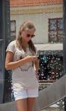 Stående av en härlig kvinnamaskinskrivning på den smarta telefonen i gatan nära en springbrunn Arkivfoton
