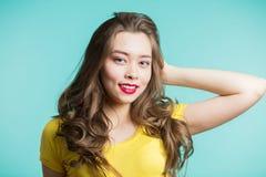 Stående av en härlig le kvinna i gul t-skjorta och röda kanter på en blå bakgrund Closeup som är horisontal, copyshastighet fotografering för bildbyråer