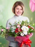 Stående av en härlig le kvinna med en stor bukett av blommor Royaltyfri Fotografi