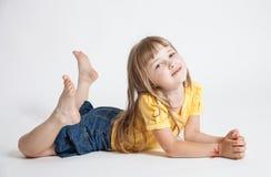 Stående av en härlig le liten flicka på golvet Arkivbild