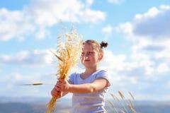 Stående av en härlig liten flicka i mitt av ett vetefält arkivbilder