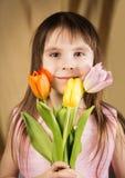 Stående av en härlig liten flicka med tre tulpan Arkivfoton