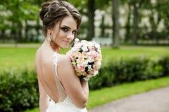 Stående av en härlig lycklig brunettbrud i för klänninginnehav för bröllop vita händer i bukett av blommor utomhus Royaltyfria Bilder