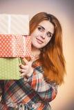 Stående av en härlig lycklig flicka med massor av gåvor i händer, en ung kvinna som rymmer en bunt av askar som slås in i dekorat arkivbilder