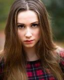 Stående av en härlig mörk blond tonårs- flicka i en skog Arkivbild