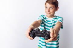 Stående av en härlig och emotionell pojke, i vars händer den modiga styrspaken som spelar lekar, visar glädje, vit bakgrund, t-sh arkivfoto