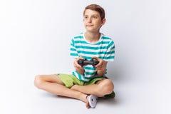 Stående av en härlig och emotionell pojke, i vars händer den modiga styrspaken som spelar lekar, visar glädje, vit bakgrund, t-sh fotografering för bildbyråer