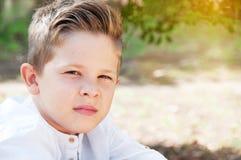 Stående av en härlig pojkecloseup Gullig skolpojke i parkera, arkivbilder