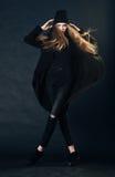 Stående av en härlig rödhårig flicka i svart kläder arkivbild