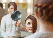 Stående av en härlig rödhårig flicka med långt hår, som ser i spegeln i skönhetsalongen royaltyfria foton