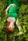 Stående av en härlig rödhårig gravid flicka i gröna dres royaltyfri fotografi