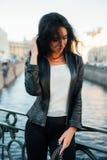 Stående av en härlig sexig brunett som poserar på en bro på en flodbakgrund Royaltyfri Foto