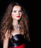 Stående av en härlig sexig elegant flicka i aftonklänning med en stor halsband med en ljus festlig makeupstudio royaltyfri foto