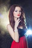 Stående av en härlig sexig elegant flickabrunett med långt hår i aftonklänning med den ljusa festliga makeupstudion royaltyfri foto