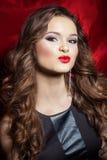 Stående av en härlig sexig elegant flickabrunett med långt hår i aftonklänning med ljus festlig makeup och röd läppstift arkivfoto