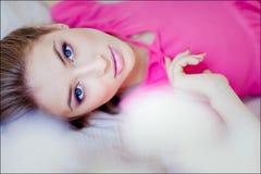 Stående av en härlig sinnlig flicka i en rosa klänning som ligger på th royaltyfria foton