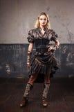 Stående av en härlig steampunkkvinna i den frodiga randiga blusen, över grungebakgrund Arkivfoto