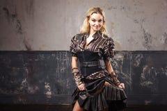 Stående av en härlig steampunkkvinna i den frodiga randiga blusen, över grungebakgrund Arkivfoton