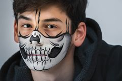 Stående av en härlig tonåring med en makeup på hans framsida i stilen av allhelgonaaftonen Royaltyfri Foto