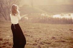 Stående av en härlig ung blond flicka i de vita sweatrarna som står med hans baksida Arkivfoto