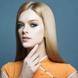 Stående av en härlig ung blond flicka i studion på en blå bakgrund, begreppet av hälsa och skönhet Royaltyfri Fotografi