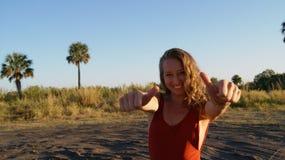 Stående av en härlig ung blond kvinnamodell som ler upp och visar tummar arkivbilder