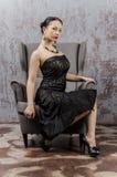 Stående av en härlig ung brunettkvinna i en svart klänning Royaltyfri Foto