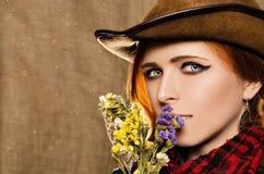 Stående av en härlig ung flicka i en cowboyhatt med lösa torkade blommor Arkivfoto