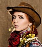 Stående av en härlig ung flicka i en cowboyhatt med lösa torkade blommor Arkivbilder