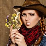 Stående av en härlig ung flicka i en cowboyhatt med lösa torkade blommor Royaltyfria Bilder