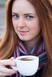 Stående av en härlig ung flicka med blåa ögon som dricker coff Arkivfoton