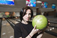 Stående av en härlig ung flicka med en bowlingklot i henne händer Flickan spelar bowling Royaltyfria Bilder