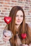 Stående av en härlig ung flicka som erbjuder en hjärta Arkivbild