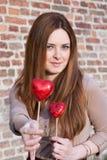 Stående av en härlig ung flicka som erbjuder en hjärta som ser fo Fotografering för Bildbyråer