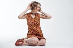 Stående av en härlig ung flicka som sitter på en vit bakgrund arkivfoton