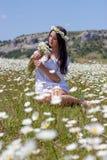 Stående av en härlig ung kvinna i kamomillfält Lycklig flicka som samlar tusenskönor En flicka som vilar i ett fält av kamomillen Arkivbilder