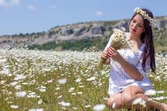 Stående av en härlig ung kvinna i kamomillfält Lycklig flicka som samlar tusenskönor En flicka som vilar i ett fält av kamomillen Royaltyfri Foto