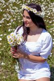 Stående av en härlig ung kvinna i kamomillfält Lycklig flicka som samlar tusenskönor En flicka som vilar i ett fält av kamomillen Royaltyfria Bilder