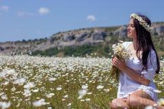 Stående av en härlig ung kvinna i kamomillfält Lycklig flicka som samlar tusenskönor En flicka som vilar i ett fält av kamomillen Arkivbild