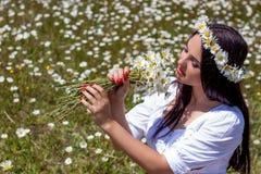 Stående av en härlig ung kvinna i kamomillfält Lycklig flicka som samlar tusenskönor En flicka som vilar i ett fält av kamomillen Royaltyfri Bild
