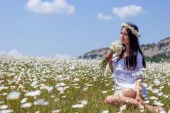 Stående av en härlig ung kvinna i kamomillfält Lycklig flicka som samlar tusenskönor En flicka som vilar i ett fält av kamomillen Fotografering för Bildbyråer