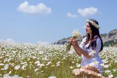 Stående av en härlig ung kvinna i kamomillfält Lycklig flicka som samlar tusenskönor En flicka som vilar i ett fält av kamomillen Royaltyfria Foton
