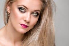 Stående av en härlig ung kvinna med lyxigt blont hår Kvinnlig framsidacloseup makeup royaltyfri bild