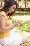 Stående av en härlig ung kvinna med telefonen Fotografering för Bildbyråer
