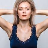 Stående av en härlig ung kvinna på en grå bakgrund royaltyfri fotografi