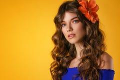 Stående av en härlig ung kvinna på en gul bakgrund, härlig blomma i hennes hår, delikat naturligt smink royaltyfri fotografi