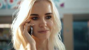 Stående av en härlig ung kvinna som använder ett smartphoneanseende vid ett glass fönster för modelagerskärm med dvärgar lager videofilmer
