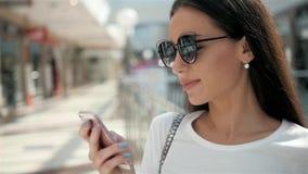 Stående av en härlig ung kvinna som använder ett smartphoneanseende vid ett glass fönster för modelagerskärm med dvärgar arkivfilmer